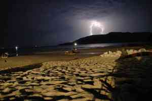 A thunder storm lights up the beach