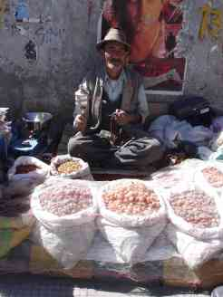 An old dried fruit and nut wallah with his prayer wheel and beads