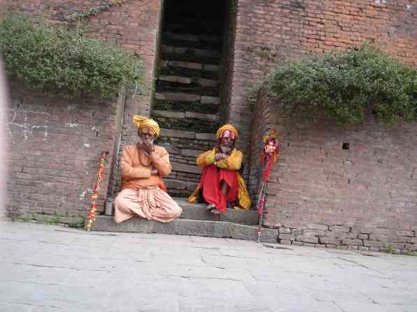 Two colourful sadhus sit by the burning ghats